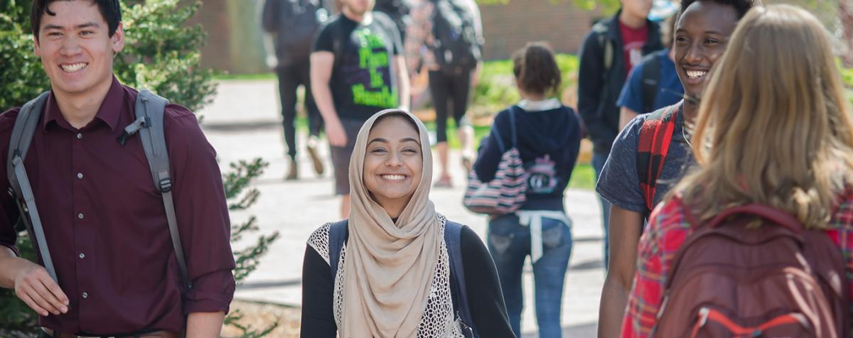 students walking on campus. Woman with headscarf smiling